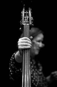 Bild på Joelle Leandre holding strings. Skärpa på handen och strängar bakom kan man se hennes ansikte fint ur fokus