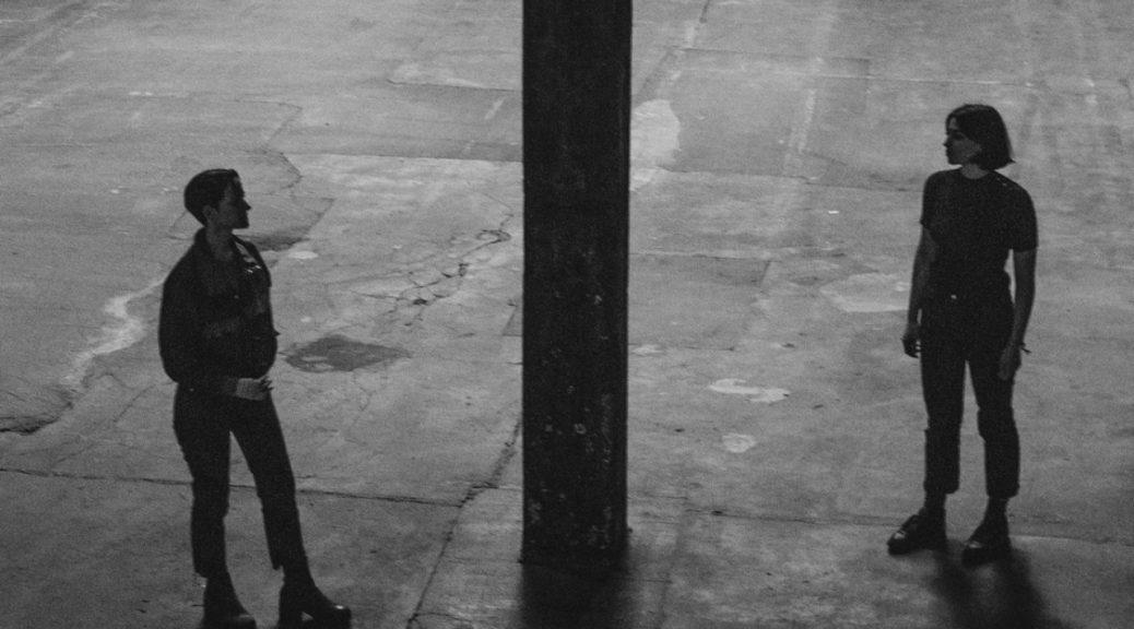 upper glossa. de två bandmedlemmarna står på var sin sida av en pelare i en industrilokal. de tittar på varandra. svartvit bild, en rå känsla.